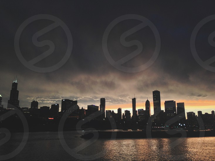 city skyline near body of water underneath gray clouds  photo