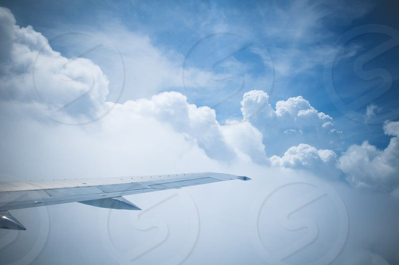 Airplane wing in clouds and blue sky photo