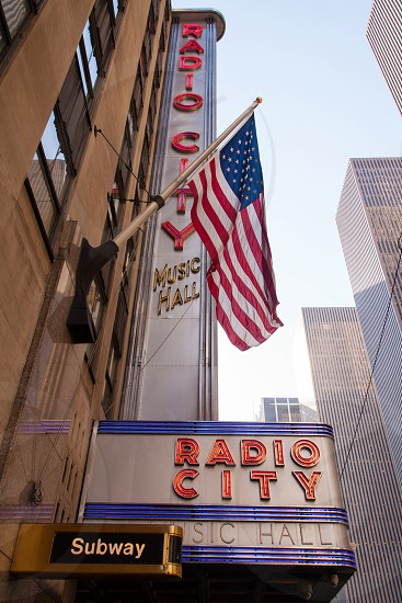 u.s. flag on metal pole attached on radio city music hall building photo