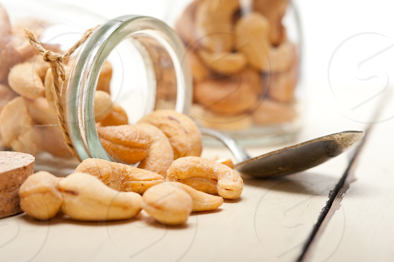 cashew nuts on a glass jar over white rustic wood table  photo