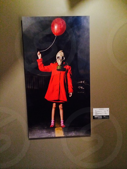 girl wearing gas mask while holding balloon on roadway painting photo