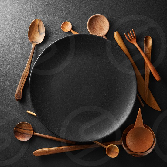 setting empty black plate and wooden spoon fork knife on a black table. photo