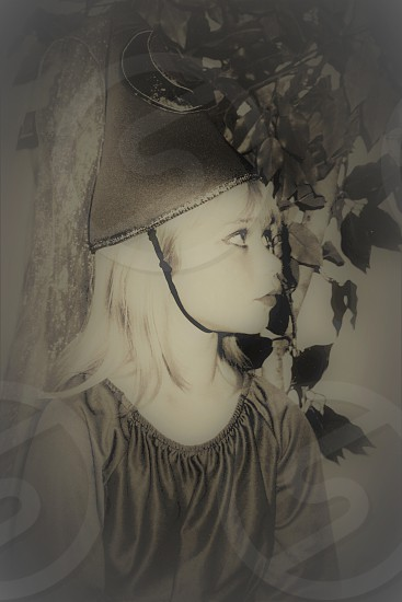 Small blond girl child in witch/wizard costume looking up away; foliage behind; profile view. photo