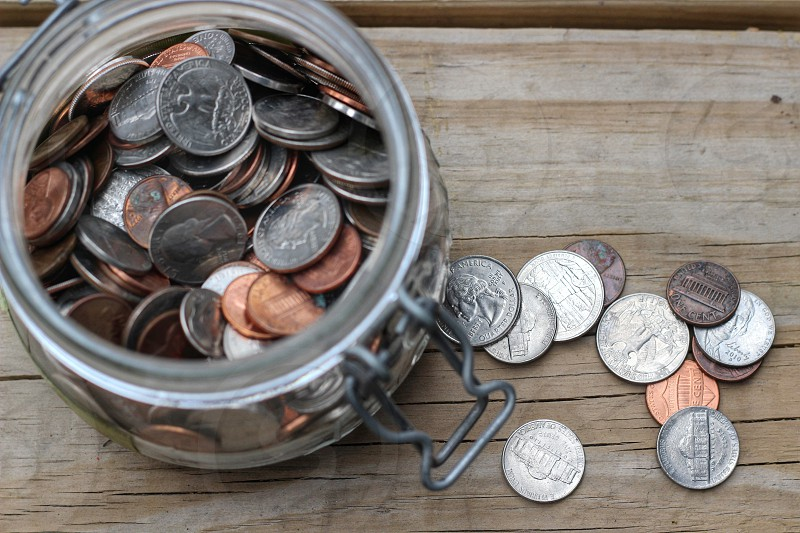 copper and silver coins on glass jar photo