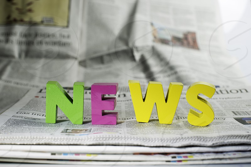 Word news on newspaper. Wooden letters photo