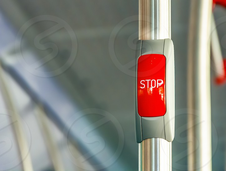 Red stop button on the metal handrail of a bus. Public transport. Public transportation photo
