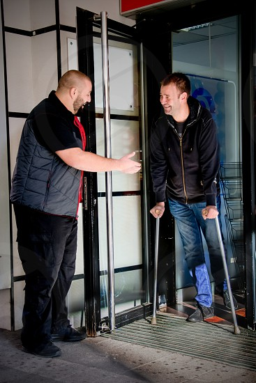 Man opening the door for another man on crutches photo