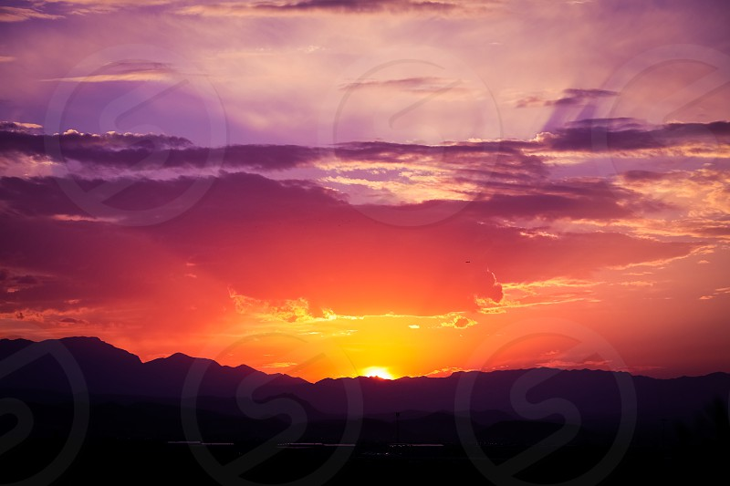 sunsetsunsunriseskytwilightnaturemountainmountainssceneryscenicviewpurpleorangelandscapelandscapesmajesticgolden hourglamorousshadowhorizonskylinecloudscloudysun rayrayssun rays photo