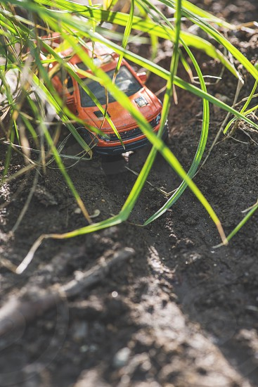 Small red off road car toy in the nature. Miniature photo