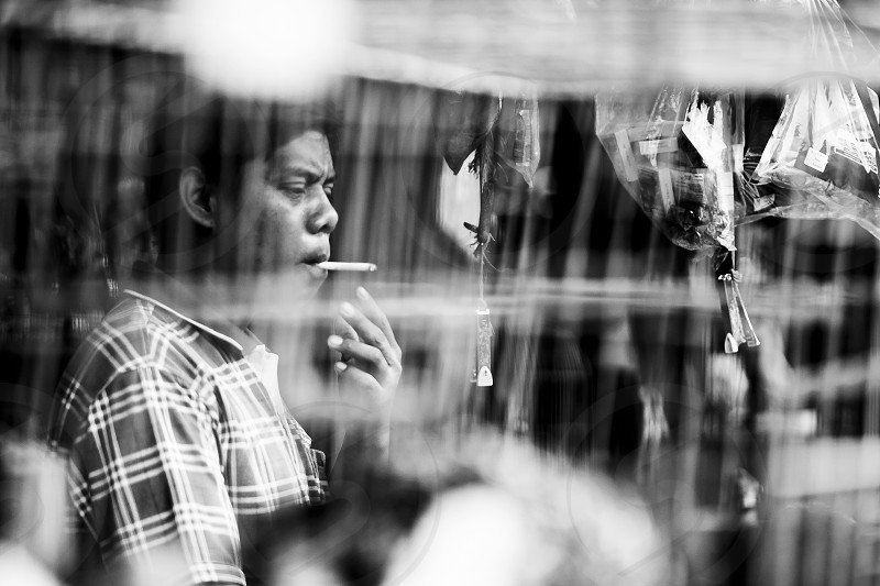 grayscale photo of man using cigarette photo