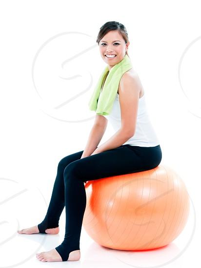 Happy fitness woman sitting on balance ball. photo