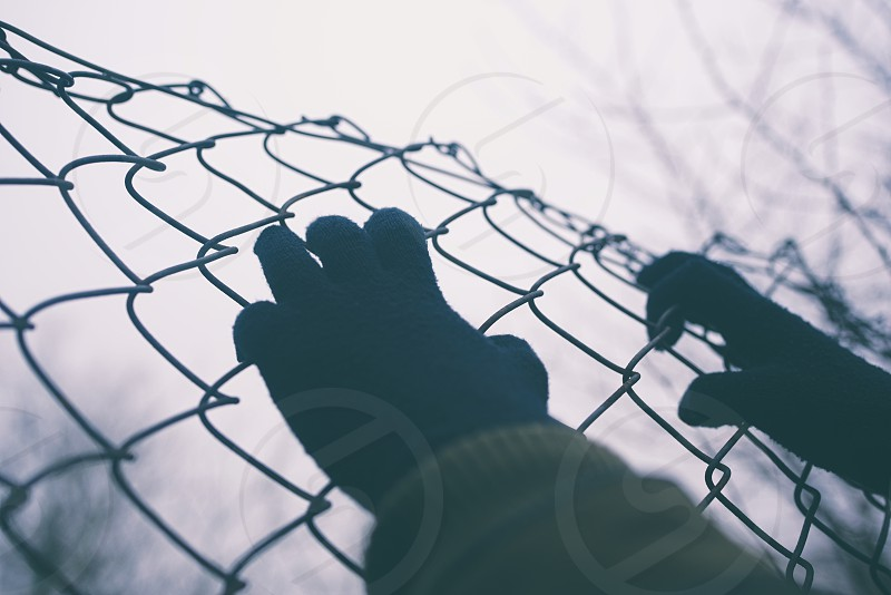 Gloved Hands on Wire Fence on an Overcast Day Closeup photo