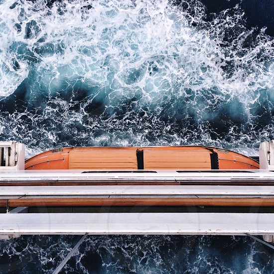 crashing sea waves below white and orange ship photo