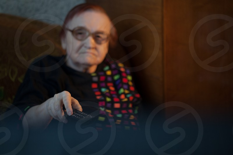 View from behind the television set of an elderly lady watching television using the remote to change channels photo