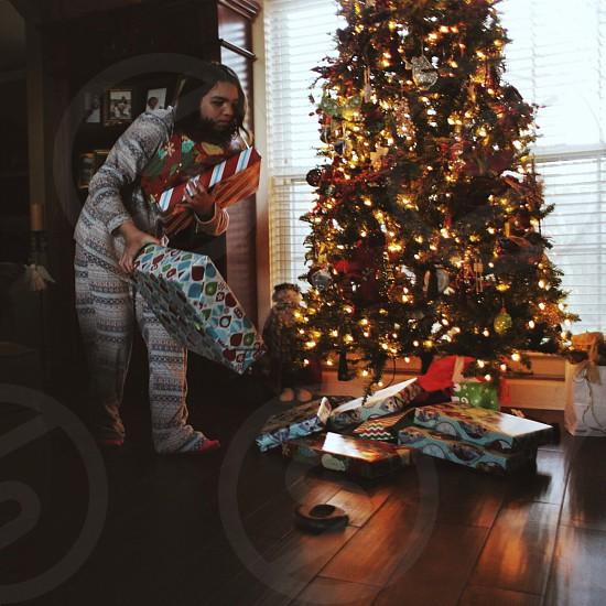 girl holding gift boxes beside christmas tree photo
