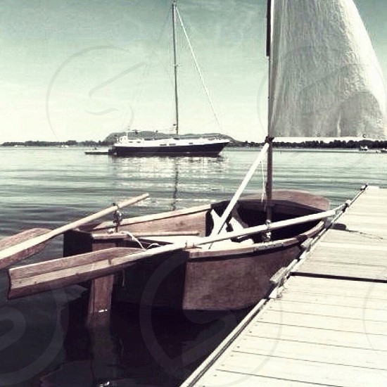 white and brown wooden sailboat beside brown wooden dock photo