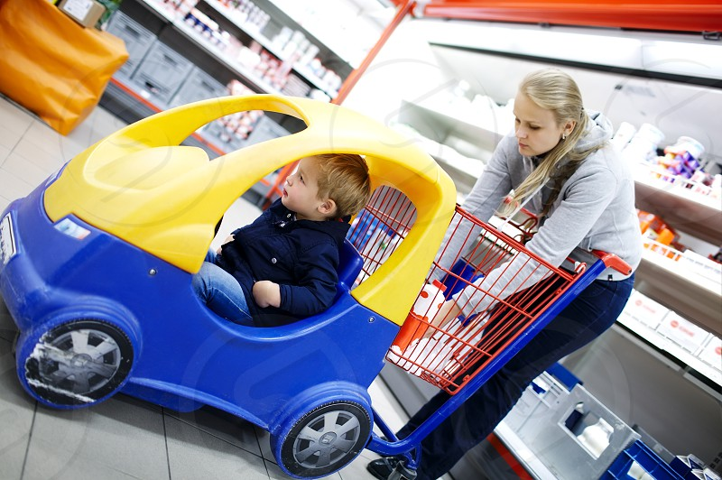 Young boy in a child friendly supermarket trolley with a colourful plastic cat attached to the front for him to ride in while his mother shops photo