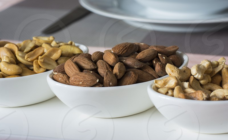 Cashew almond and peanuts in small oval bowls photo