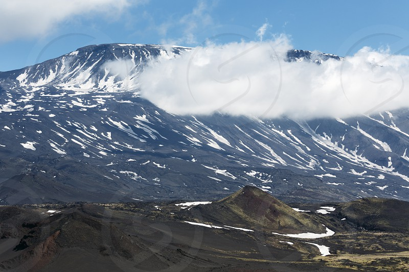Volcanic landscape of Kamchatka Peninsula: beautiful summer view of cone of active Plosky Tolbachik Volcano and clouds partially hiding the top of volcano. Eurasia Russian Far East Kamchatsky Region Klyuchevskaya Group of Volcanoes. photo