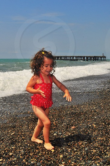girl in red and white polka dot swimsuit walking on grey rocky beach next to dark green ocean under blue sky photo