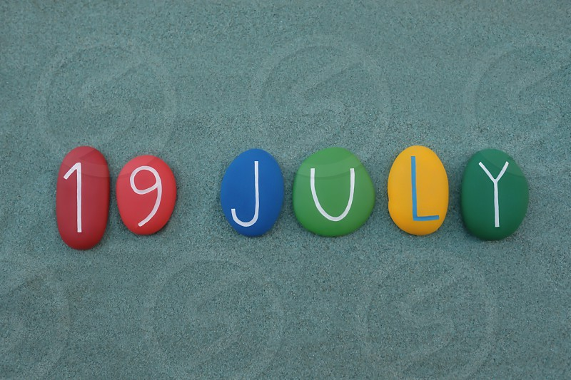 19 July calendar date composed with multi colored stones over green sand photo