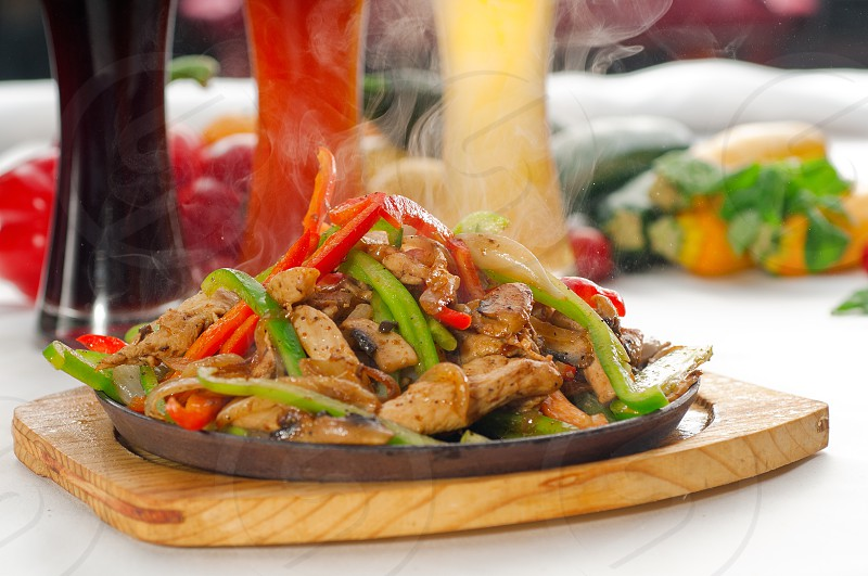 original fajita sizzling smoking hot served on iron plate with selection of beer and fresh vegetables on background MORE DELICIOUS FOOD ON PORTFOLIO photo