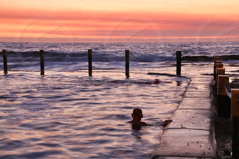 Beach pool sunrise swimmer silhouette  photo