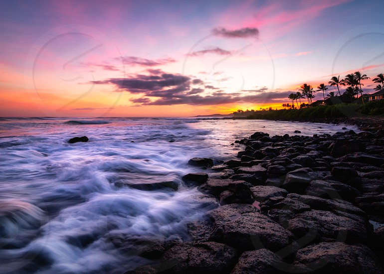 Sunset at a rocky beach with vivid warm colors and beautiful skies. photo
