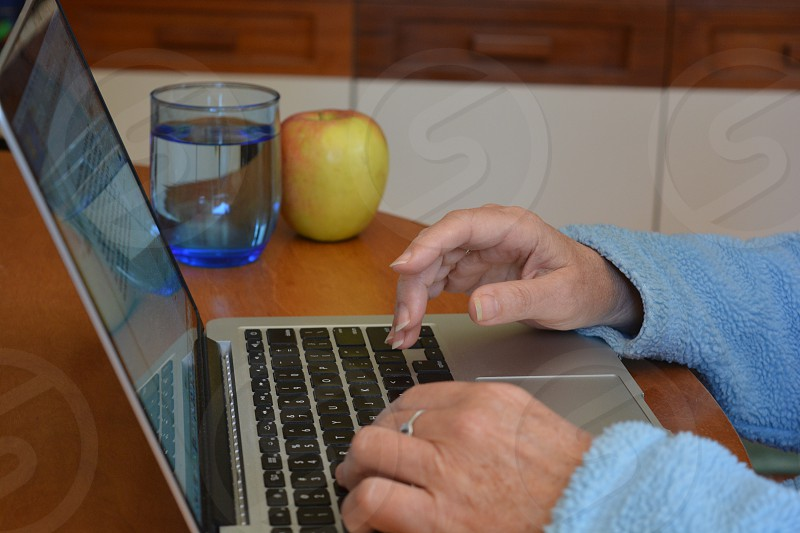 Woman typing on a laptop keyboard. with an apple and a glass of water on the desk photo