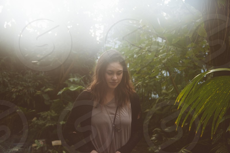 woman in grey shirt and black cardigan standing under trees in woods photo