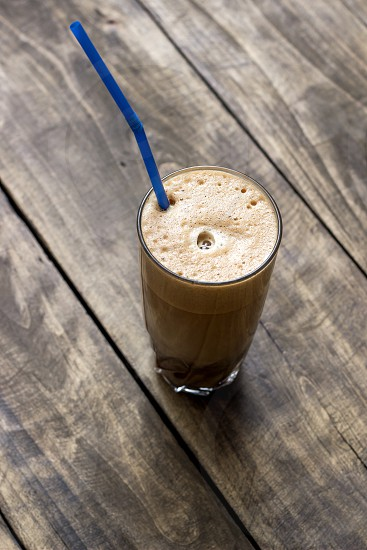 Greek coffee cold Frappe drink on a wooden table photo
