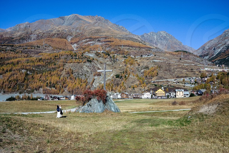Nun Taking a Photograph of the Cross at Cogne in Italy photo