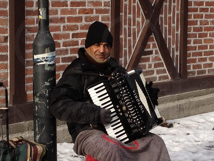 man wearing a black jacket playing an accordion on the street photo