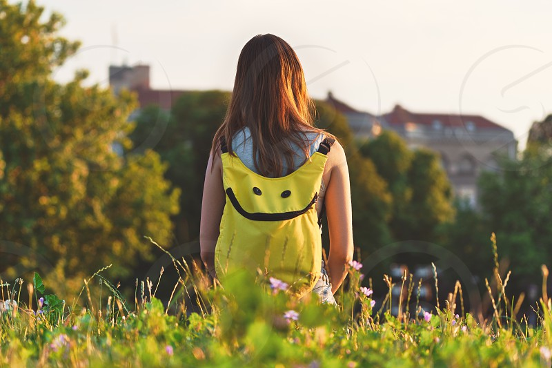 Girl tourist with a backpack looking forward to the city on nature in summer in sunny weather photo