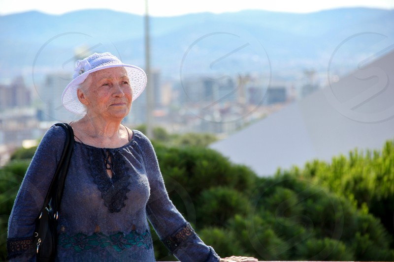Portrait of a cute elderly lady in a knitted sun hat walking along a tourist city on a sunny day. photo