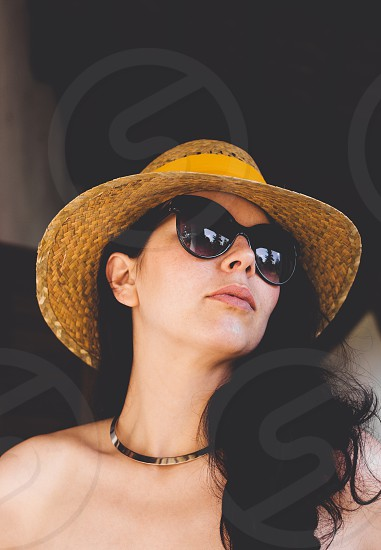 woman in black sunglasses and straw sun hat photo