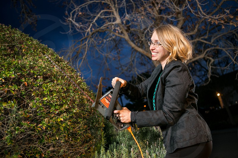 A woman works on her yard with a hedge trimmer while wearing a business casual outfit during twilight. photo