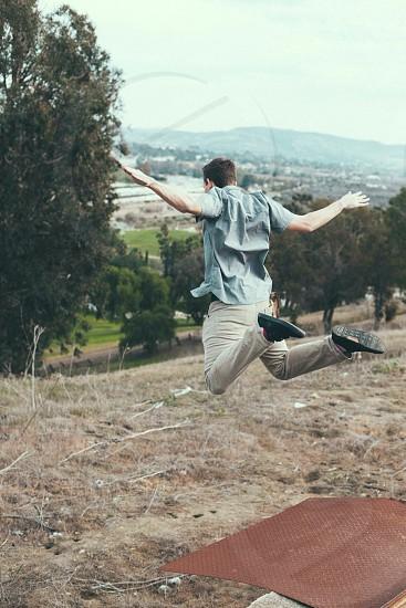 man jumping off metal sheet on hill photo