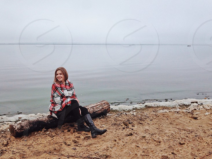 woman wearing red black and white plaid shirt and black pants sitting on driftwood at the shore below gray sky during daytime photo