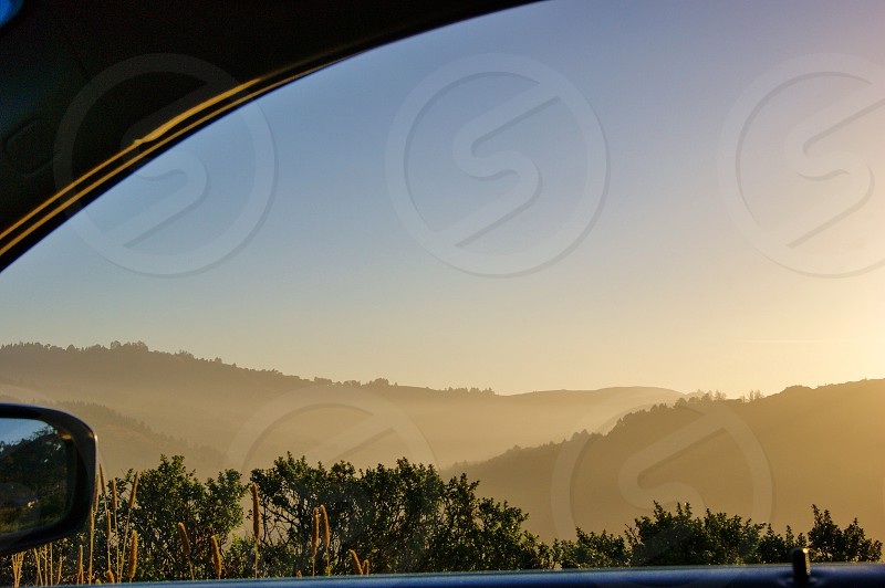 Sunrise road trip California foggy morning mountains sun rays car window Muir Beach coast highway 1  photo