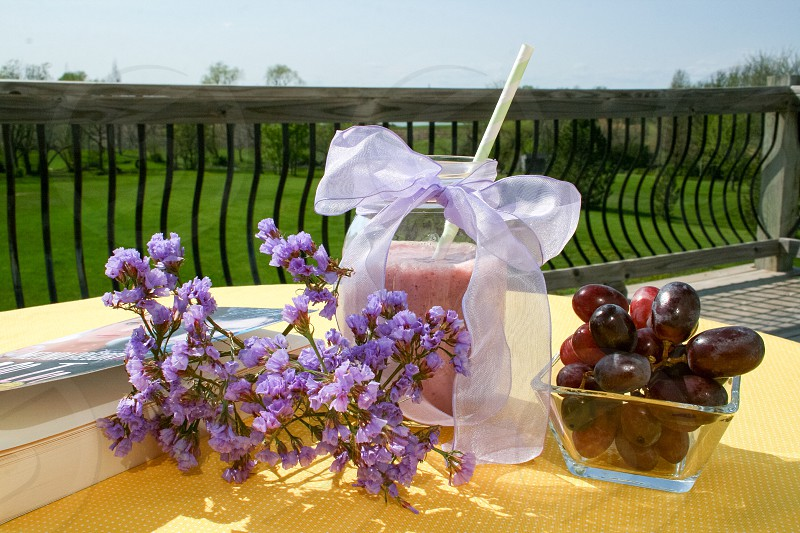 Lavender flowers berry fruit smoothie red grapes and book on yellow tablecloth photo
