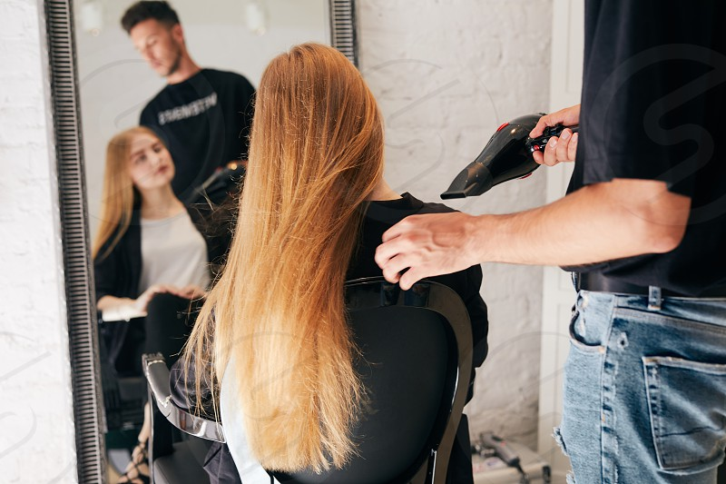 Pretty girl doing hair cut on hairdresser shop photo