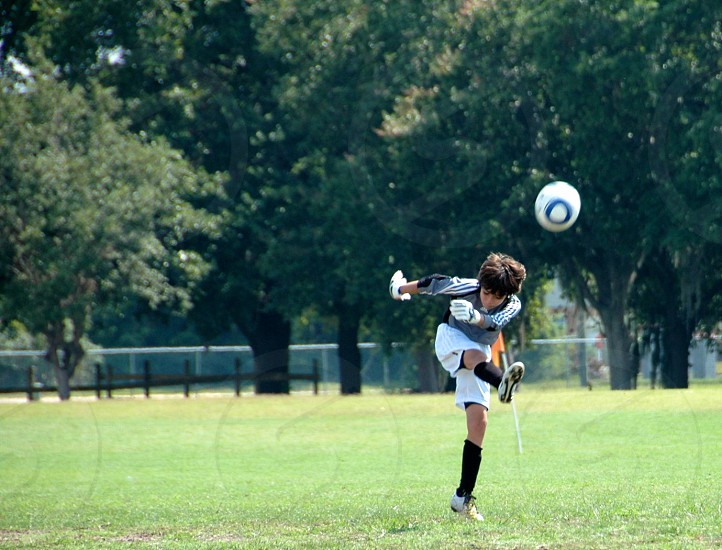 boy in white jersey shorts kicks soccer ball during daytime photo