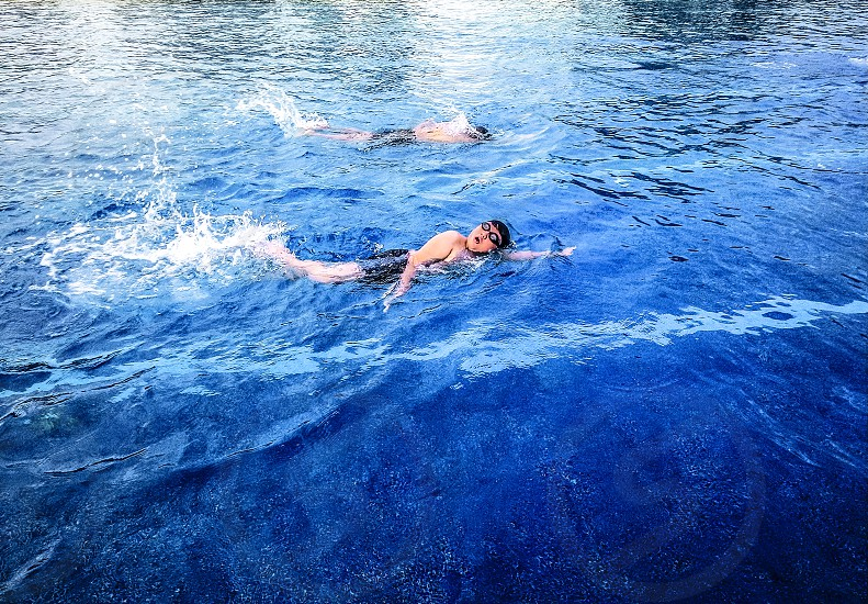 Kids swimming in outdoor pool photo
