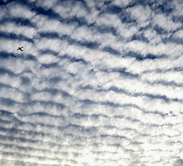 An airplane flying against rippled clouds photo