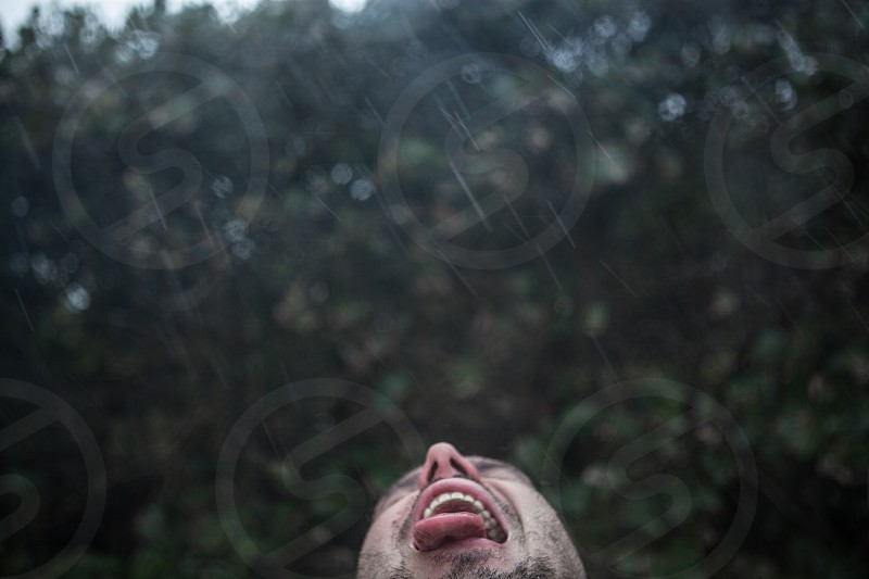 man drinking water in a tropical rain photo