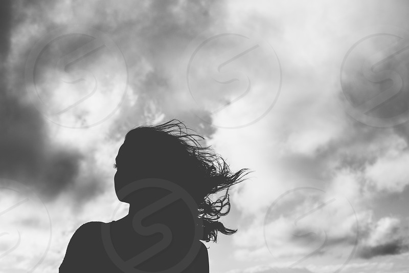 silhouette female woman girl lady femininem hair wind windy moody sky clouds dark black whimsical thought think process pensive creative lifestyle love alone lonely solitude beauty beautiful shadows darkness photo