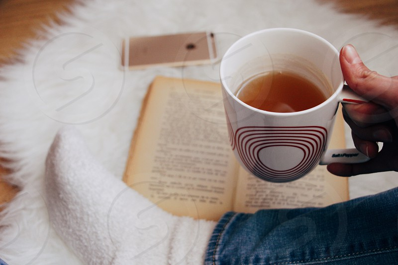 photo of white red ceramic mug held by person near gold iphone 6 on white fur rug beside opened book photo