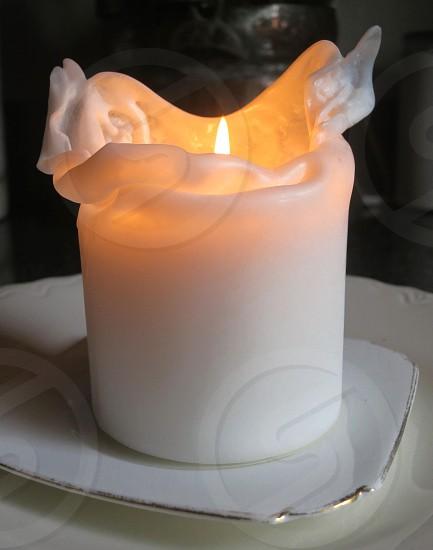 White candle burning on white plate photo