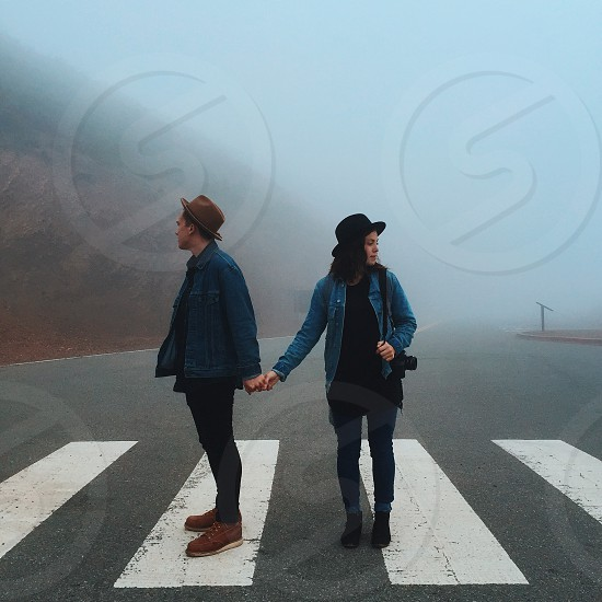 couple in blue denim jackets standing on pedestrian lane in middle of highway in foggy day photo